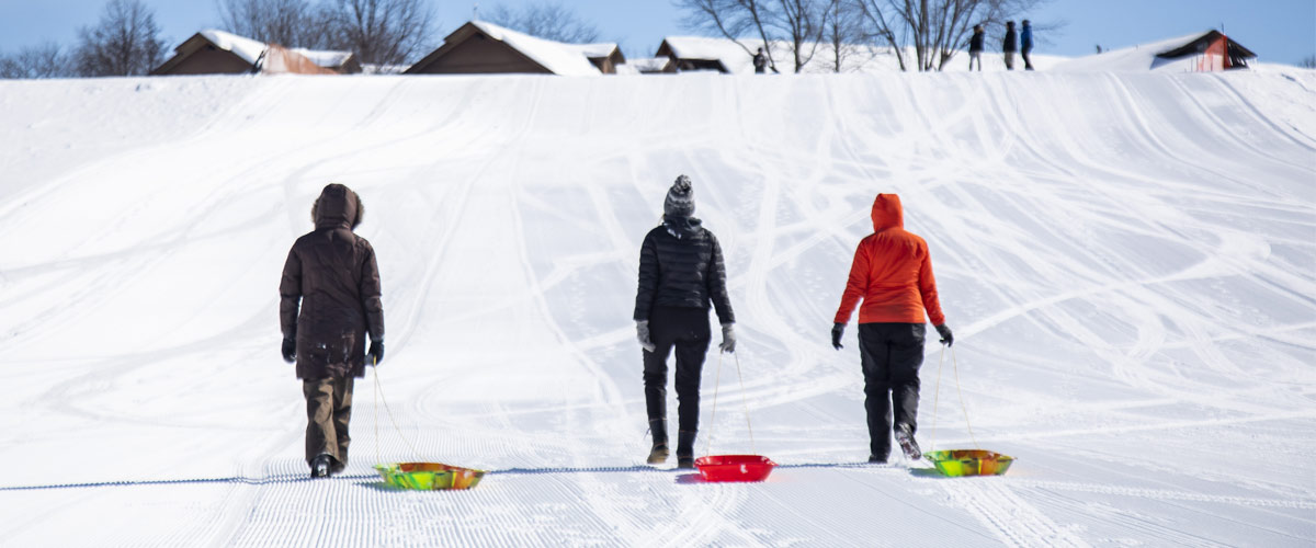 Three adults walk up a sledding hill pulling brightly colored plastic sleds behind them.