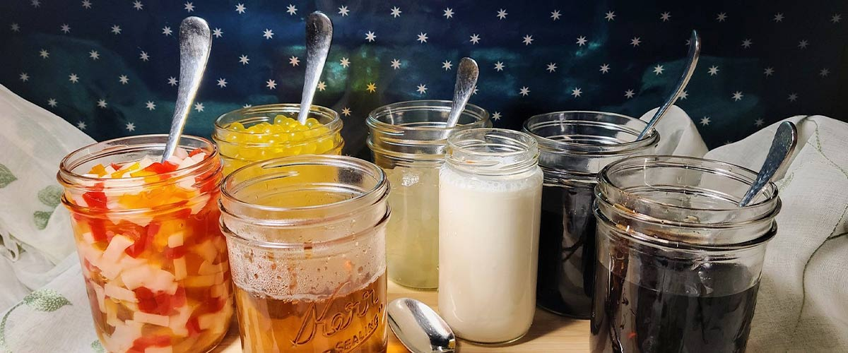 group of mason jars filled with boba tea toppings and spoons