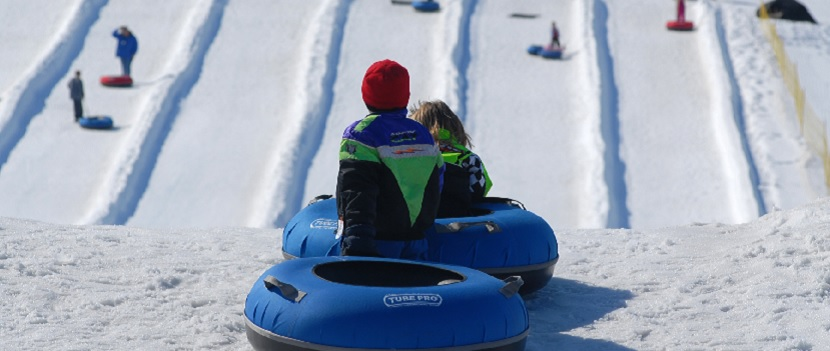 Two kids ready to go down the hill in snow tubes.