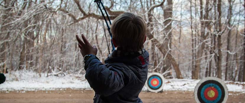 A boy aims a bow and arrow at archery targets in the winter.