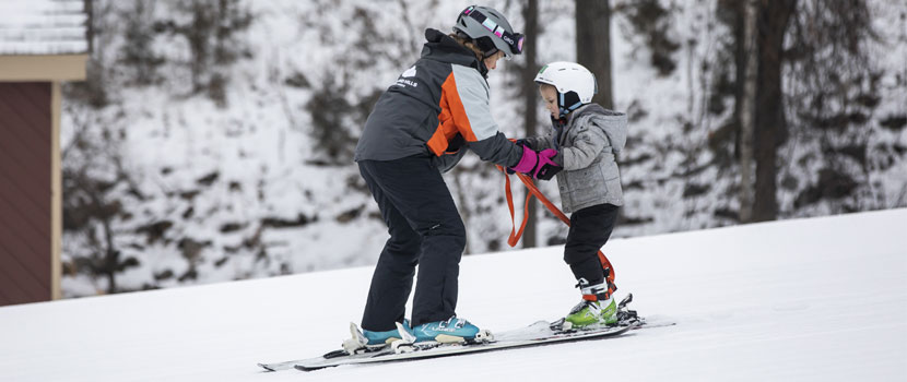 An instructor teaches a child how to downhill ski.