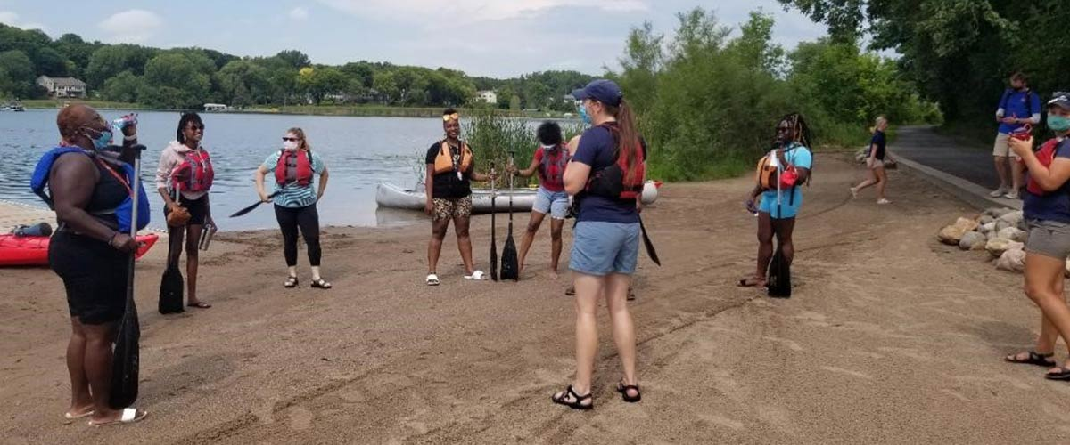 A group of people gets a canoe lesson from a Three Rivers staff person at Fish Lake Regional Park.
