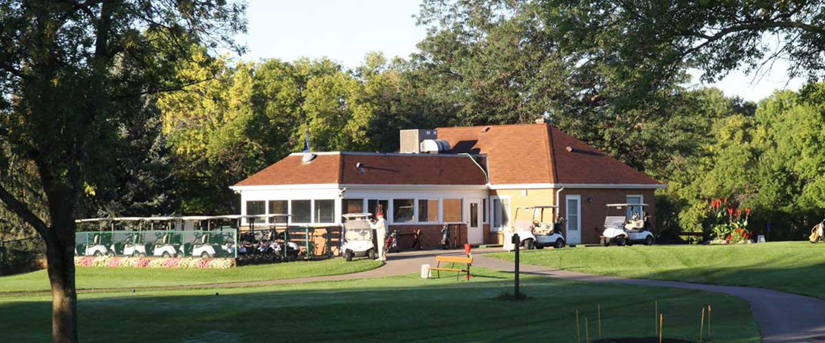 Golf carts are lined up on the back side of the Hyland Greens Golf Course clubhouse.
