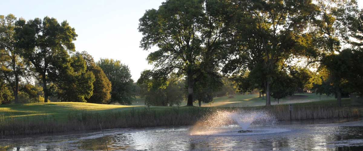 A fountain sprays water in a pond at Hyland Greens Golf Course.