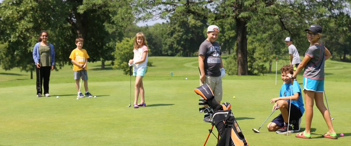 A group of kids take a golf lesson at Hyland Greens Golf Course.
