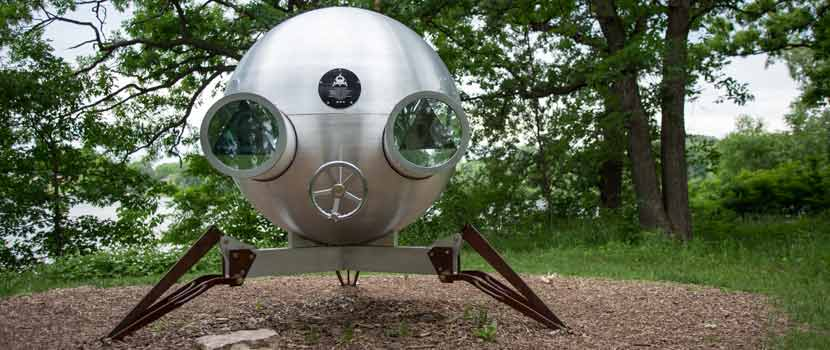 A metal sculpture on three legs that looks like a space ship.