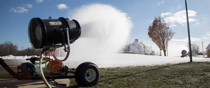 machine making and blowing snow over grassy park