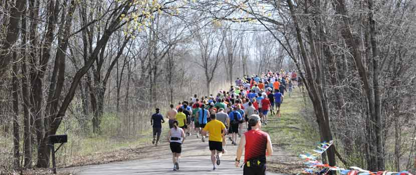 a group of runners running down a wooded trail in the spring.