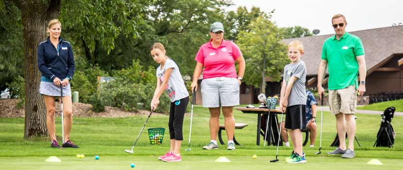 Three adults stand behind two kids as they learn how to golf.