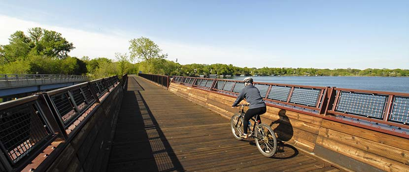 A man rides a bike across a wooden bridge in the fall.