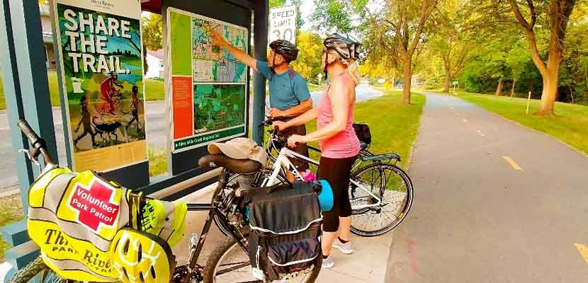 two bikers looking at a trail map next to a paved trail