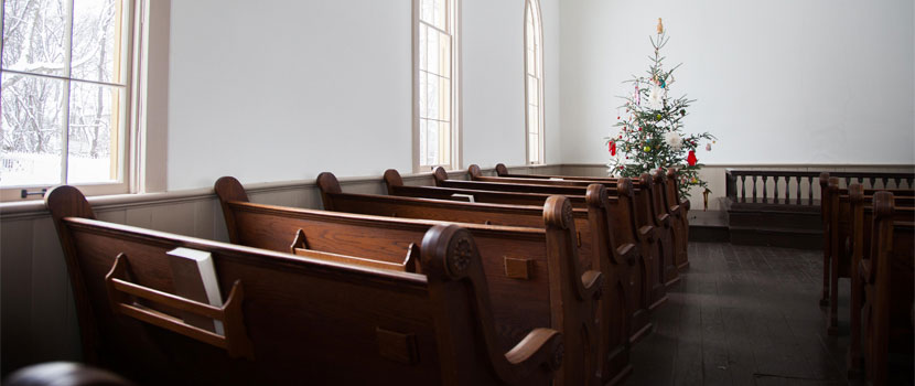 inside of an church with empty wooden pews facing a Christmas tree at the front