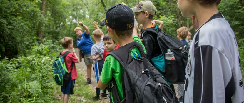 A group of boys stand in a line on a trail while a counselor counts them.