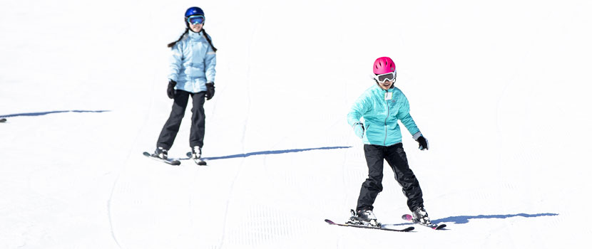 Two girls smile while they ski down a hill.