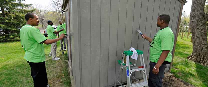 Two young men paint a shed
