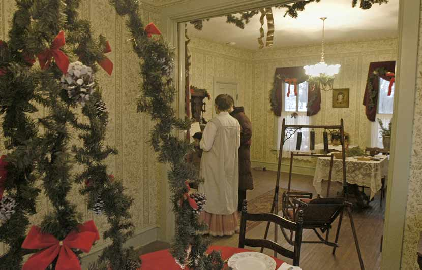 the setting of an 1800s house decorated in greenery for the December holiday season