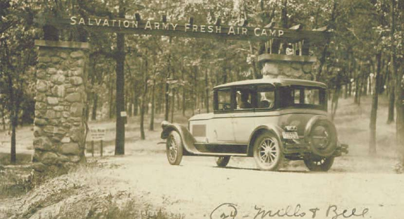 "A historic photo of a car driving under a sign that says ""Salvation Army Fresh Air Camp."""