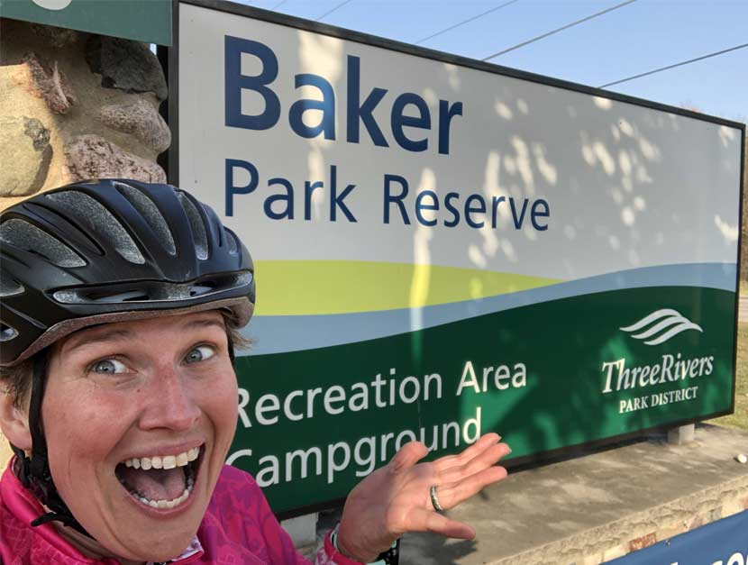 A woman takes a selfie in front of a park sign for Baker Campground.