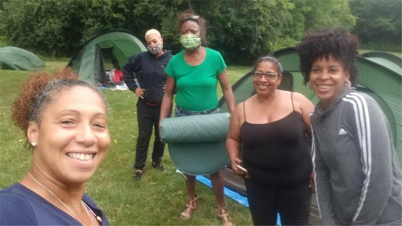 Five women take a selfie outside while camping.