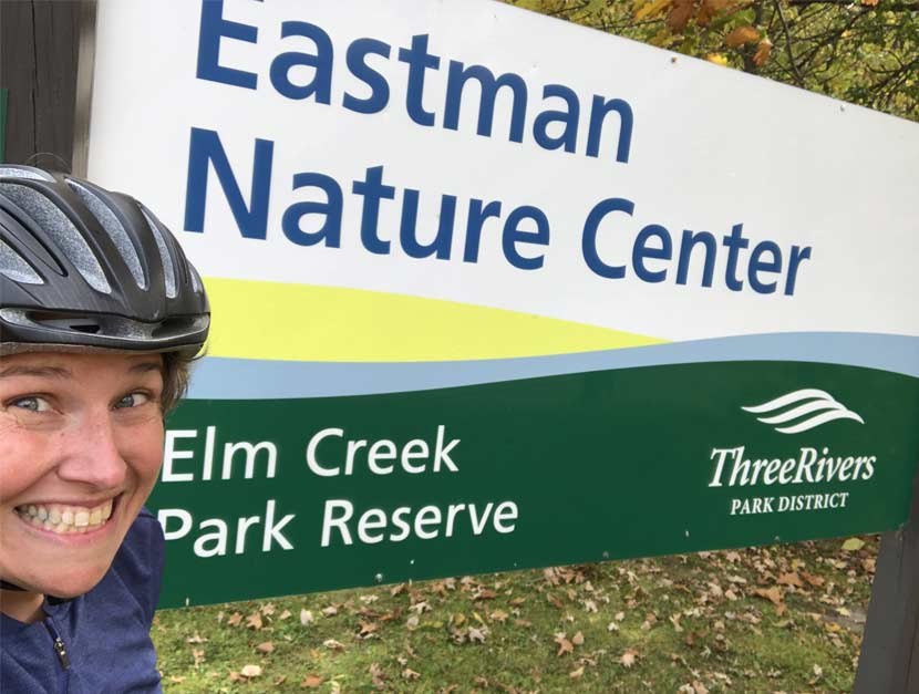 A woman takes a selfie in front of a park sign for Eastman Nature Center at Elm Creek Park Reserve.