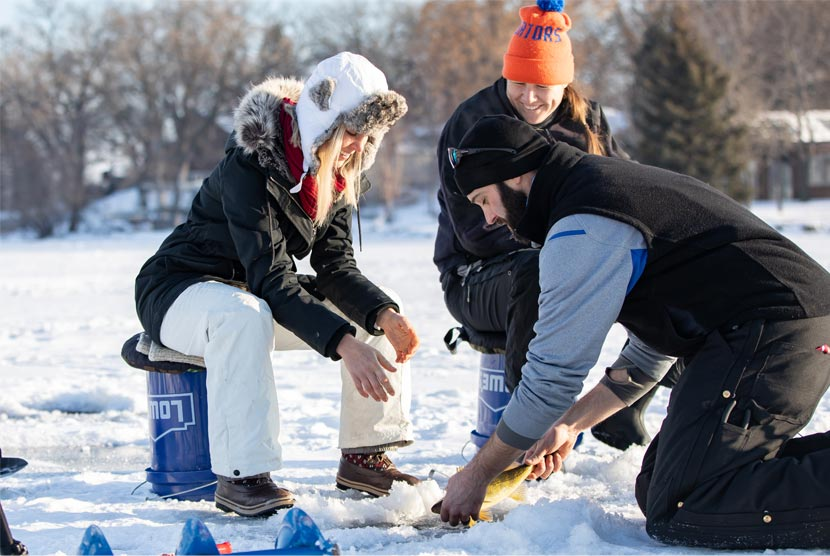 Three people pull a fish out of a lake while ice fishing.
