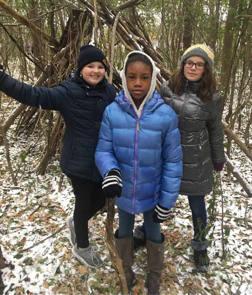 Three girls stand outside in the woods in the winter.