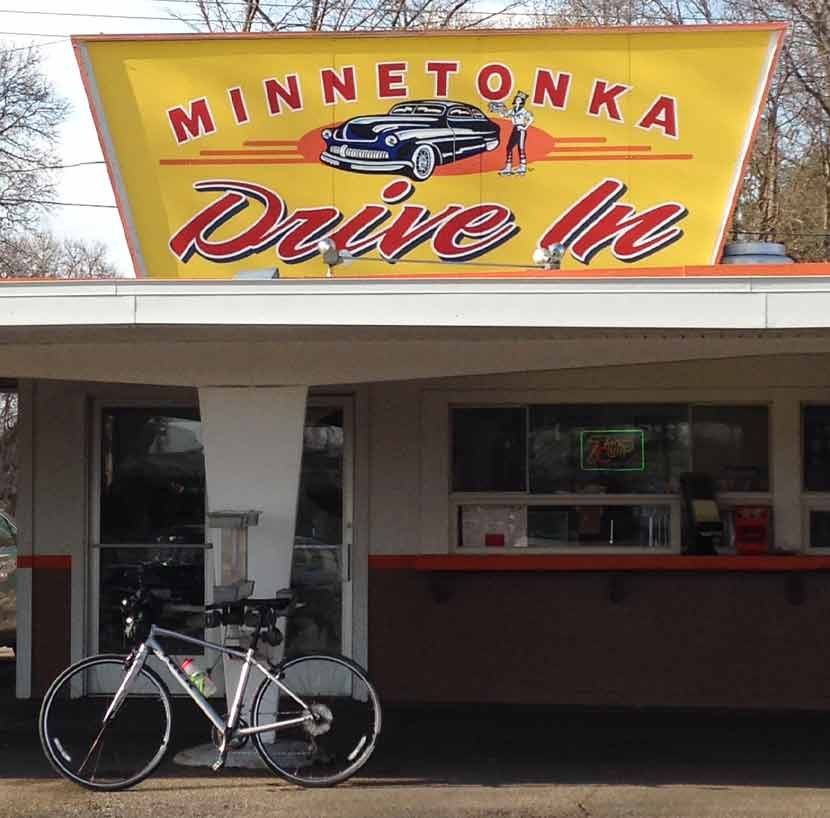 a white bike parked in front of a drive in with a large yellow sign on top that says Minnetonka Drive in.
