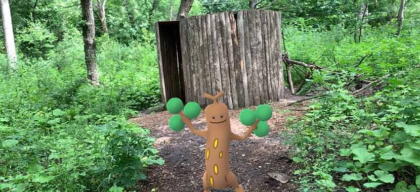 A tree-like video game character stands in front of a wooden sculpture at a park.