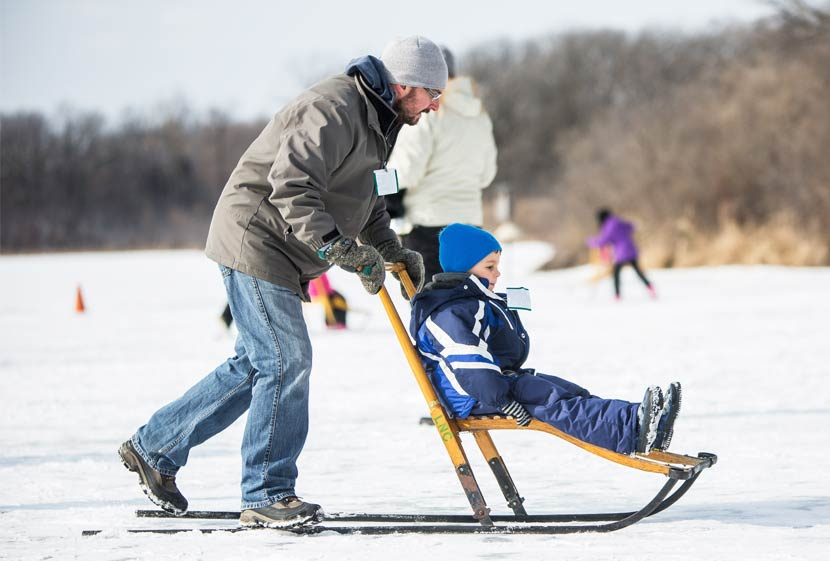 A man pushes a small boy across a frozen lake on a kicksled.