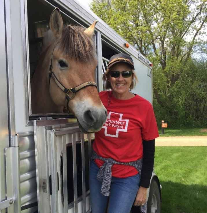 woman in a red volunteer shirt standing next to a horse trailer with her horse