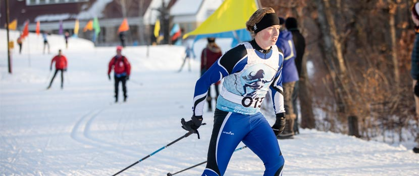 A woman competes in a cross-country ski race. Other racers can be seen in the distance behind her.