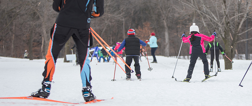 Several kids ski down a cross-country trail