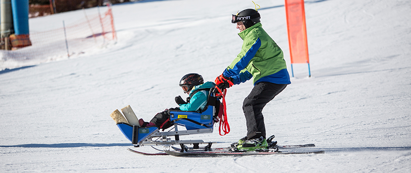 An adapted skier reaches the bottom of the hill