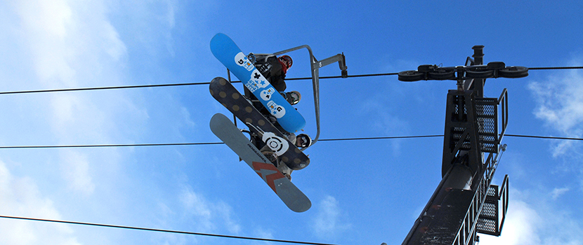 Looking up at the bottom of snowboards on the chairlift