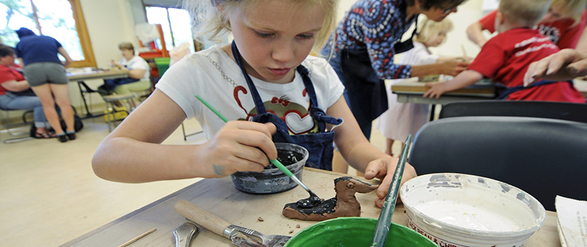 a young girl paints a piece of pottery