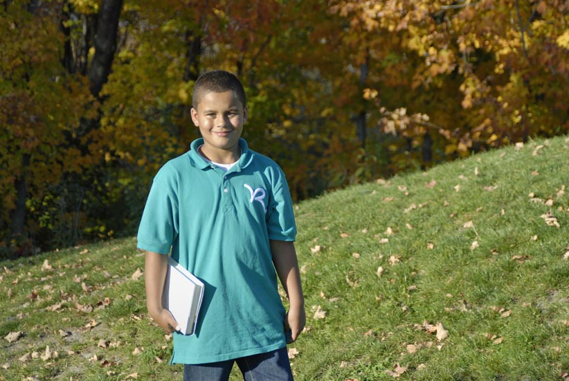 Boy standing in wooded area