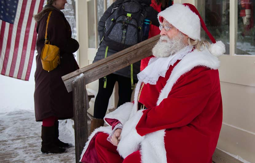 a man dressed as Santa Claus sitting on a front stairway