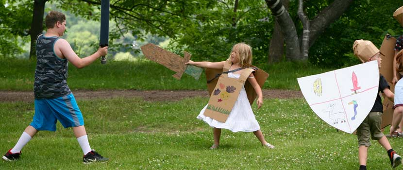 Kids at summer camp wearing pretend armor and holding a cardboard sword.