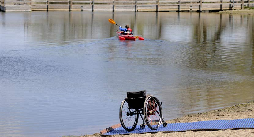 a wheelchair is on the shore of the lake and an adapted kayaker paddles away from the shore.