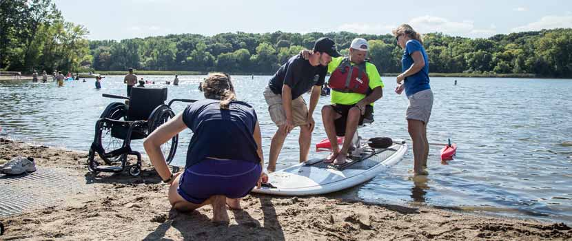 three rivers staff help a man onto an adapted paddleboard. his wheelchair is in the sand next to them.