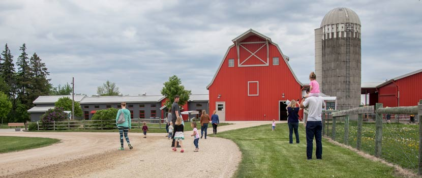 people walking on a dirt road toward a red barn.
