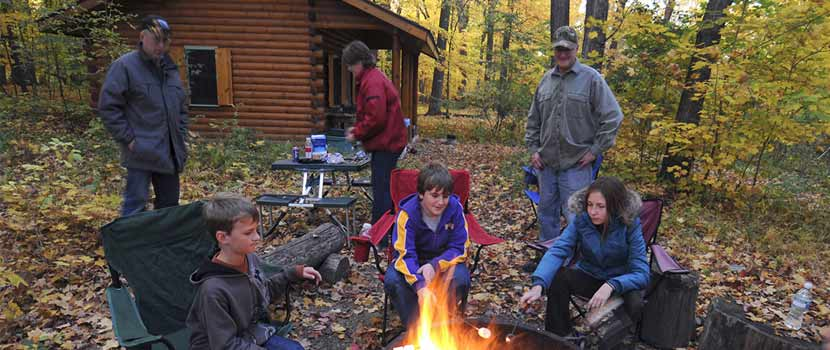 a family sitting around a campfire in the fall in front of a log cabin.