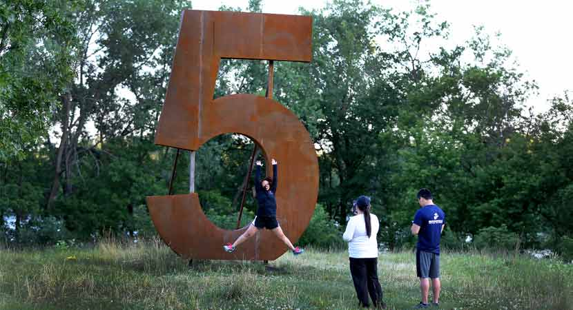 a person jumps in front a metal 5 sculpture while two others take her photo.