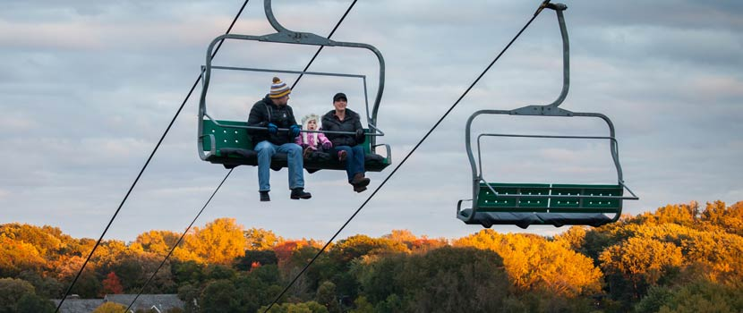 chairlift rides over tree tops of fall colors