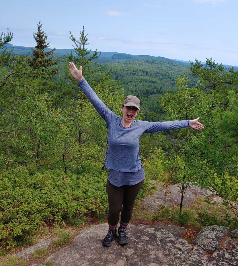 A woman spreads her arms wide and smiles as she stands on a mountain.