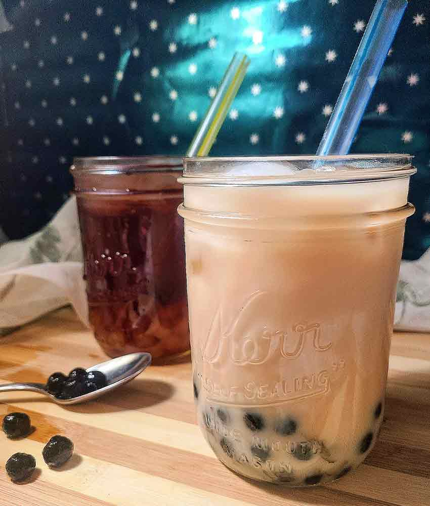 two mason jars filled with creamy boba tea