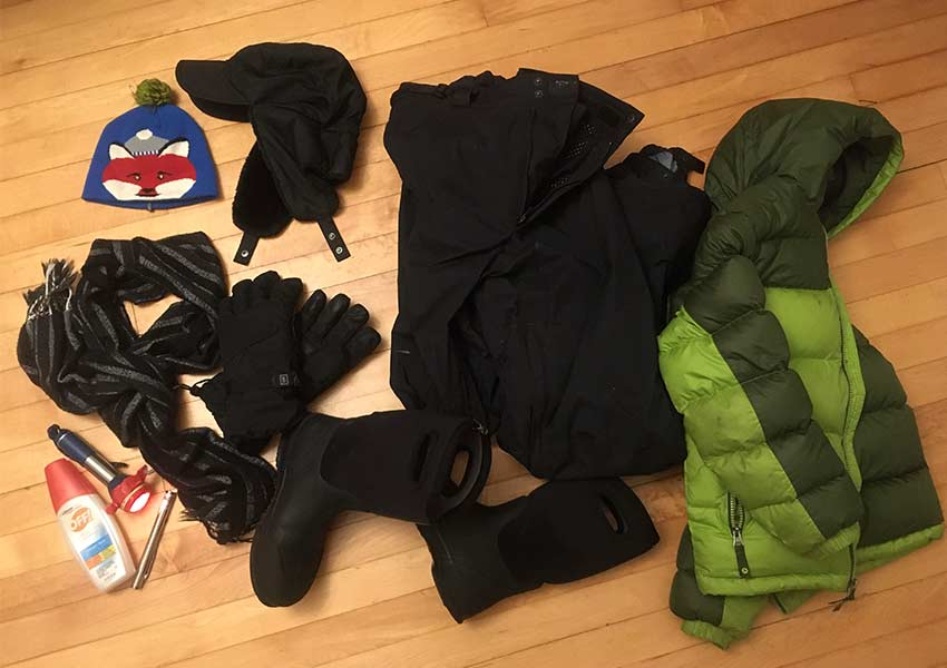 aerial photo of winter hat, coat, snow pants, gloves, bug spray and flashlight