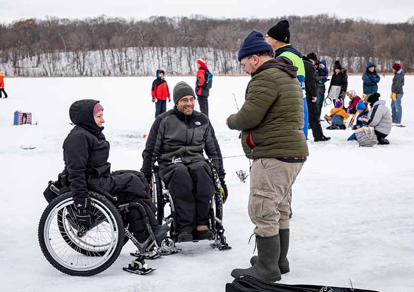 a man and a woman dressed in full winter layers in wheelchairs next to a man standing ice fishing on a frozen lake