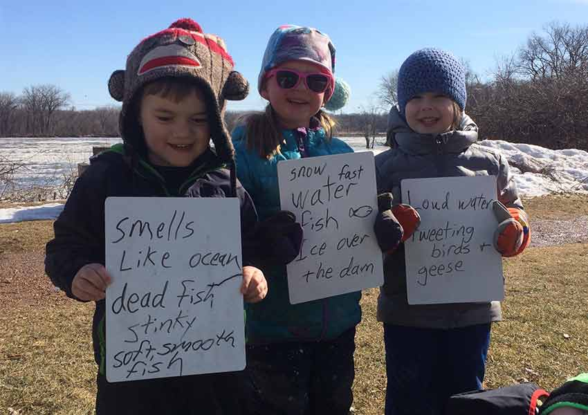 kids holding signs about what they think the river smells like