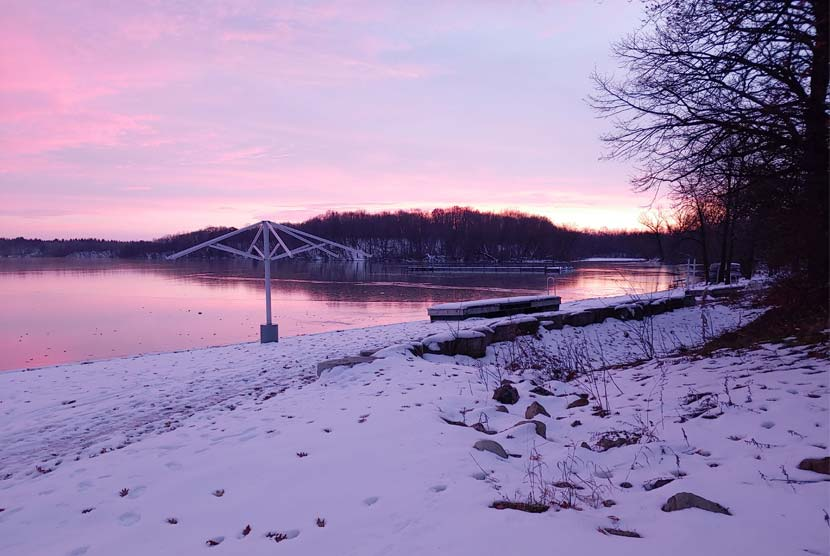 A pink and purple sunset over a lake in the winter.